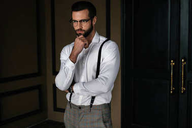 handsome bearded pensive man in white shirt and suspenders