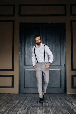 handsome elegant man posing in white shirt and suspenders against door