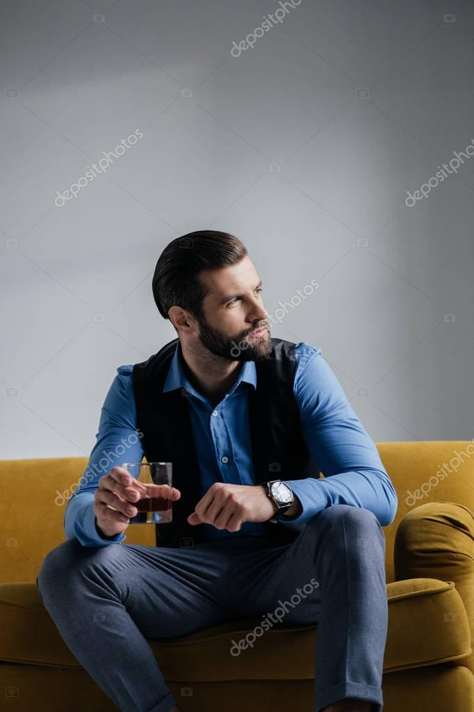 stylish man holding alcohol drink and sitting on yellow sofa