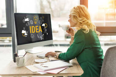 middle aged businesswoman using desktop computer with idea icons on screen and drinking coffee at workplace