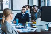 Fotografie usmívající se multikulturní podnikatelé při pohledu na kolegy v kanceláři