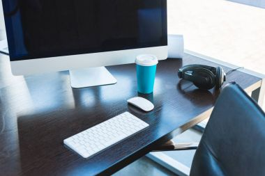 table with computer, keyboard and cup of coffee in office