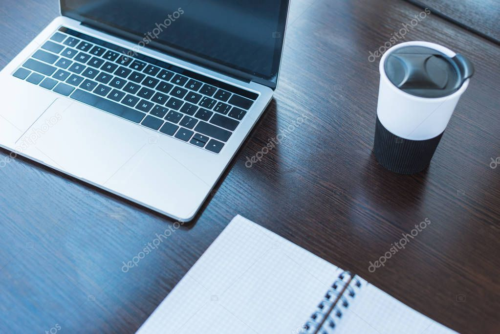 high angle view of laptop and cup of coffee on table in office