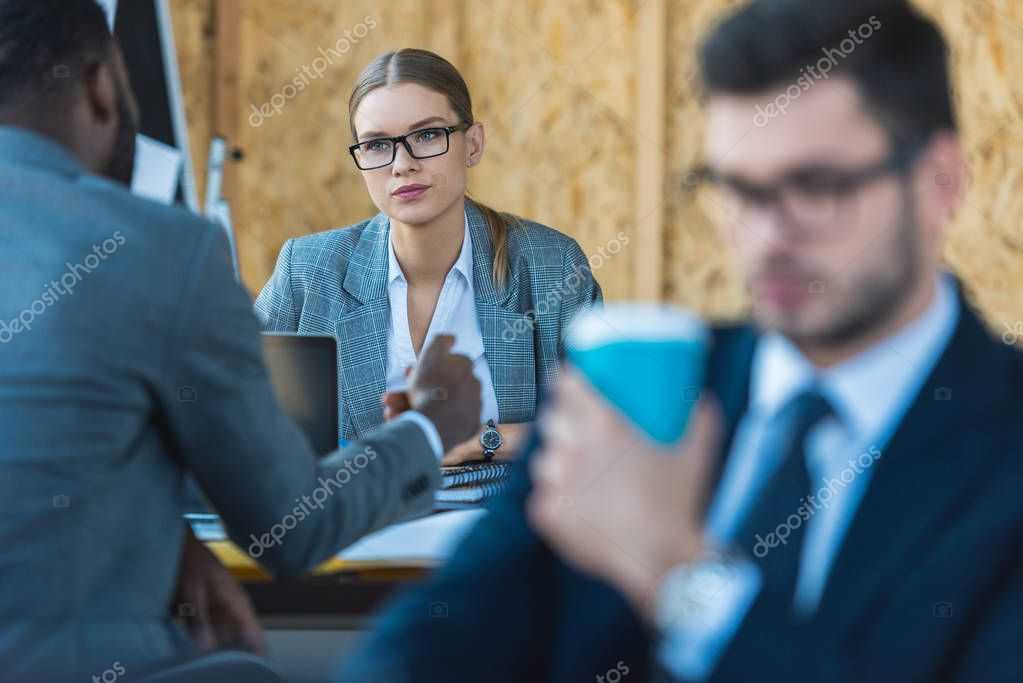 multicultural businesswoman and businessman talking in office