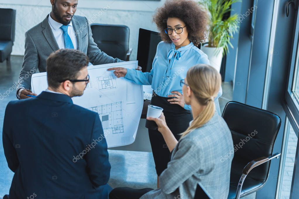 multicultural businesspeople looking at blueprint in office