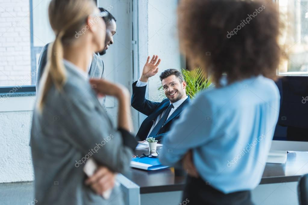 smiling businessman waving hand to multicultural colleagues in office