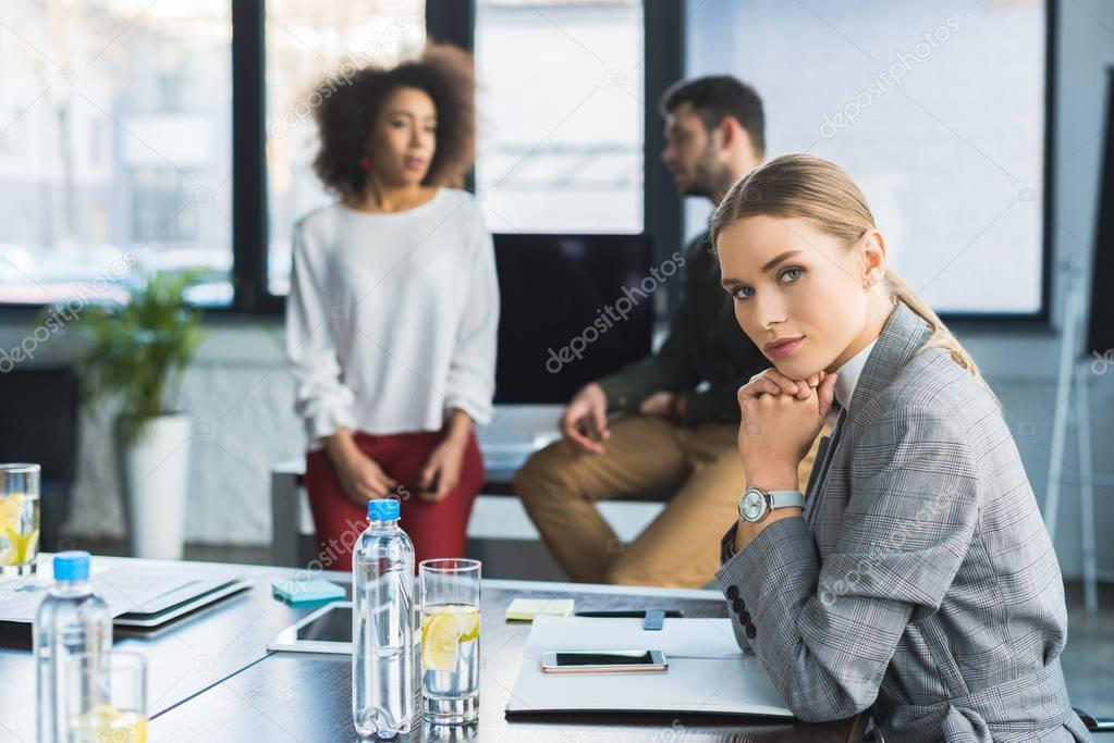 pensive businesswoman sitting at table in office and looking at camera