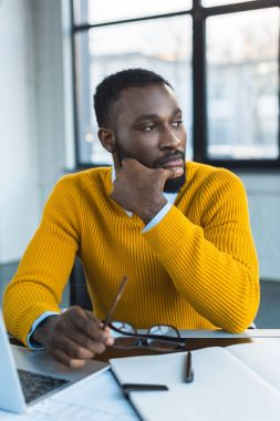 pensive african american businessman looking away in office
