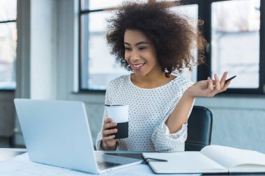 happy african american businesswoman holding cup of coffee and looking at laptop in office