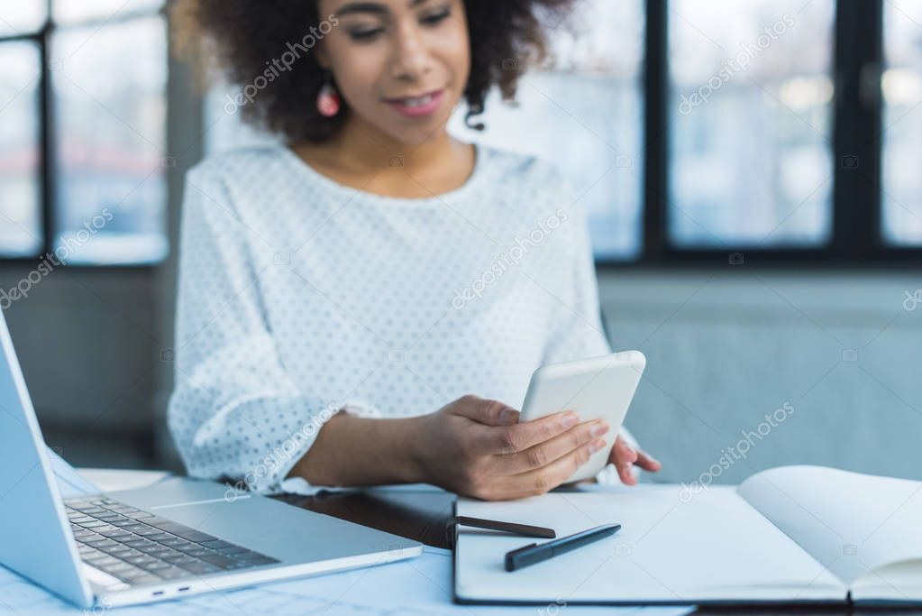 african american businesswoman using smartphone in office