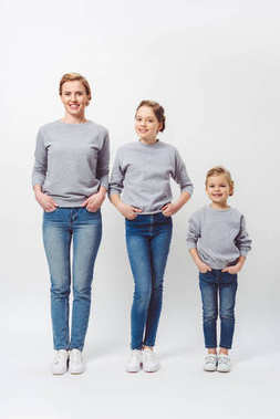 smiling mother and daughters of different generations in similar clothing with hands in pockets isolated on grey