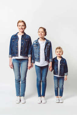 happy family in similar denim clothing standing in row and holding hands isolated on grey