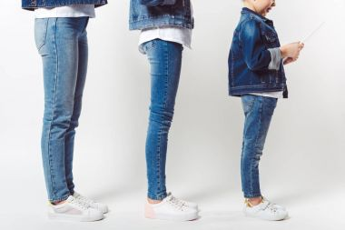 partial view of family and kid with tablet in similar denim clothing standing in row isolated on grey