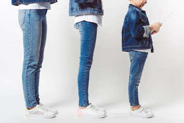 Partial view of family and kid with tablet in similar denim clothing standing in row isolated on grey stock vector