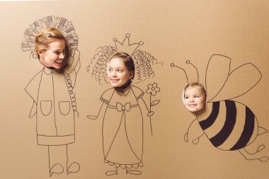 partial view of smiling mother and daughters with heads in cardboard paper with pictures