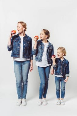 smiling mother and daughters of different generations in similar clothing with fresh apples isolated on grey