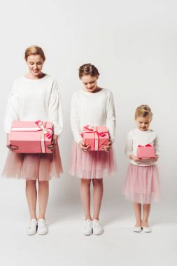 smiling mother and little daughters in similar pink tutu tulle skirts with wrapped gifts isolated on grey