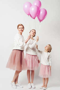 smiling mother and daughter in similar clothing with pink balloons isolated on grey
