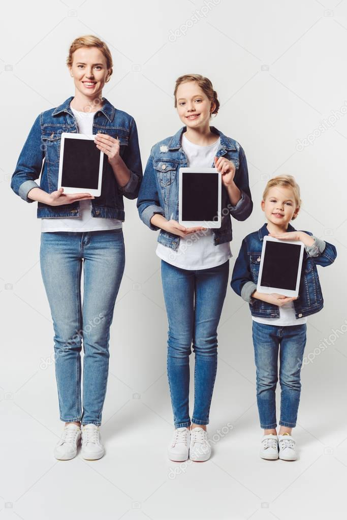 smiling family in similar denim clothing showing tablets with blank screens in hands isolated on grey