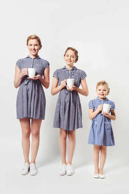 smiling mother and daughters in similar dresses with cups in hands isolated on grey