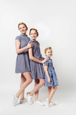 mother and daughters in similar dresses standing in row on white