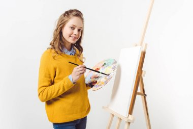 happy teen female painter in yellow sweater with paint brush and palette near easel with blank canvas on white