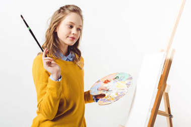 Beautiful teen female painter in yellow sweater with paint brush and palette stock vector