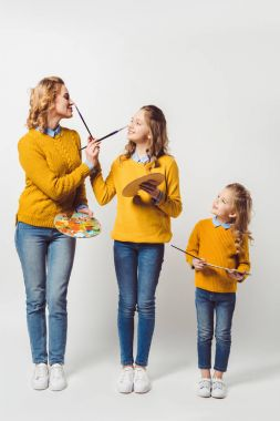 playful mother and daughters with paint brushes and palettes on white
