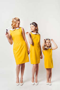 stylish mother and daughters in similar retro style yellow dresses on white