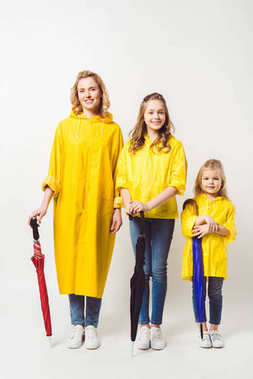 mother and daughters in yellow raincoats with umbrellas on white