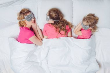 top view of mother and daughters with sleeping masks in shape of cat faces sleeping together in bed