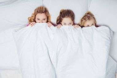 top view of mother and daughters hiding under blanket in bed