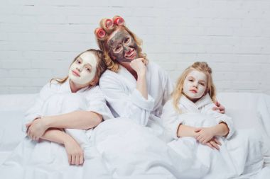 mother and daughters in bed with beauty facial masks