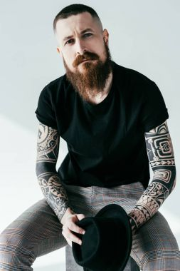 handsome bearded tattooed man looking at camera on white