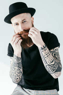 bearded tattooed man twisting mustache and looking at camera isolated on white