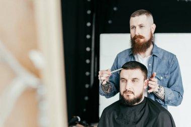 barber looking at customer haircut in mirror at barbershop