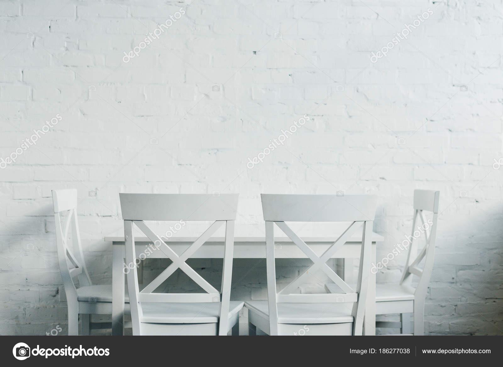 Interieur van diner kamer met houten tuinset voor bakstenen muur