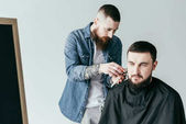 Fotografie barber trimming client beard at barbershop isolated on white