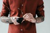 Fényképek körülvágott kép, tetovált férfi takarítás üvegek elszigetelt fehér