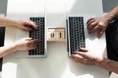 Ansicht von männlichen und weiblichen Händen beim Drucken auf Laptops mit Holzkalender zwischen