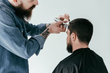 Cropped image of barber shaving hair at barbershop isolated on white stock vector
