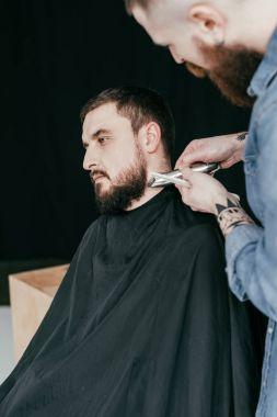 Barber trimming customer beard at barbershop stock vector