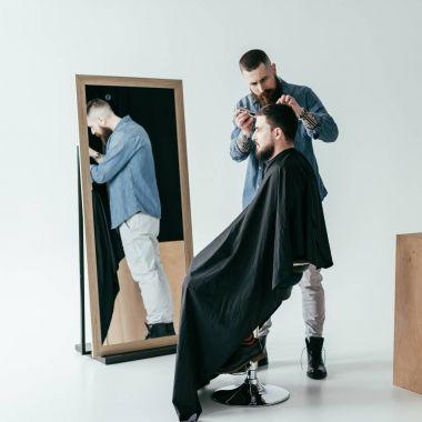 side view of barber shaving customer hair at barbershop