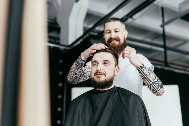 barber styling customer hair at barbershop