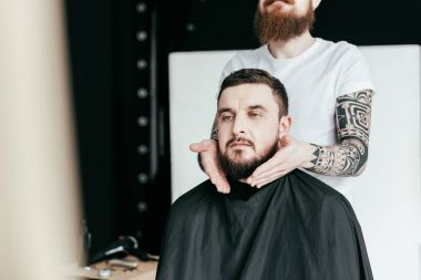 Cropped image of barber styling customer beard at barbershop stock vector