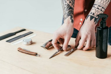 cropped image of tattooed barber putting equipment on table isolated on white