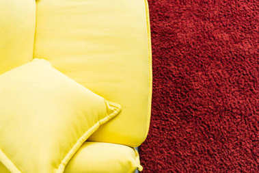 Top view of yellow leather couch and red fluffy rug