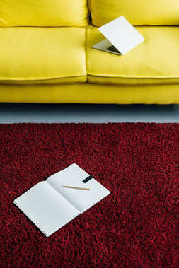 Half-closed laptop on yellow couch and textbook with pencil on rug