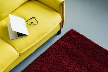 Half-closed laptop and eyeglasses on yellow leather couch