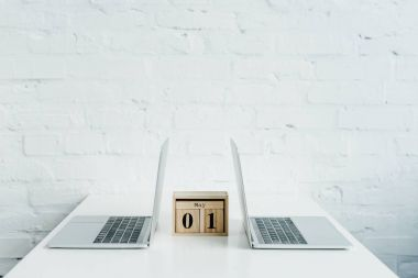 Wooden calendar between two laptops on white table